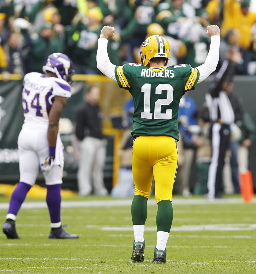 Photo - Green Bay Packers' Aaron Rodgers reacts in front of Minnesota Vikings' Jasper Brinkley (54) after Rodgers threw a touchdown pass during the first half of an NFL football game Sunday, Dec. 2, 2012, in Green Bay, Wis. (AP Photo/Mike Roemer)