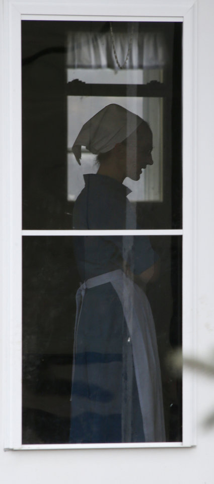 Photo - In this photo made on Tuesday, Jan. 29, 2013, an Amish woman stands in the doorway of the home of Sam Mullet Sr., in Bergholz, Ohio. Mullet is one of sixteen men and women facing sentencing Friday, Feb. 8, 2013 in beard-cutting attacks on fellow Amish in Ohio. The defendants want leniency so they can return to their homes and farms, to teach their sons a trade and their daughters how to sew, cook and keep house. (AP Photo/Keith Srakocic)