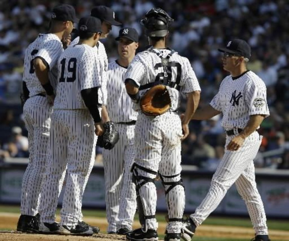 Photo - New York  Yankees manager Joe Girardi, right, approaches the pitchers mound to pull pitcher Chien-Ming Wang from the game in the second inning against the  Cleveland  Indians during a Major League Baseball game Saturday, April 18, 2009 at  Yankee Stadium in New York. (AP Photo/Julie Jacobson)