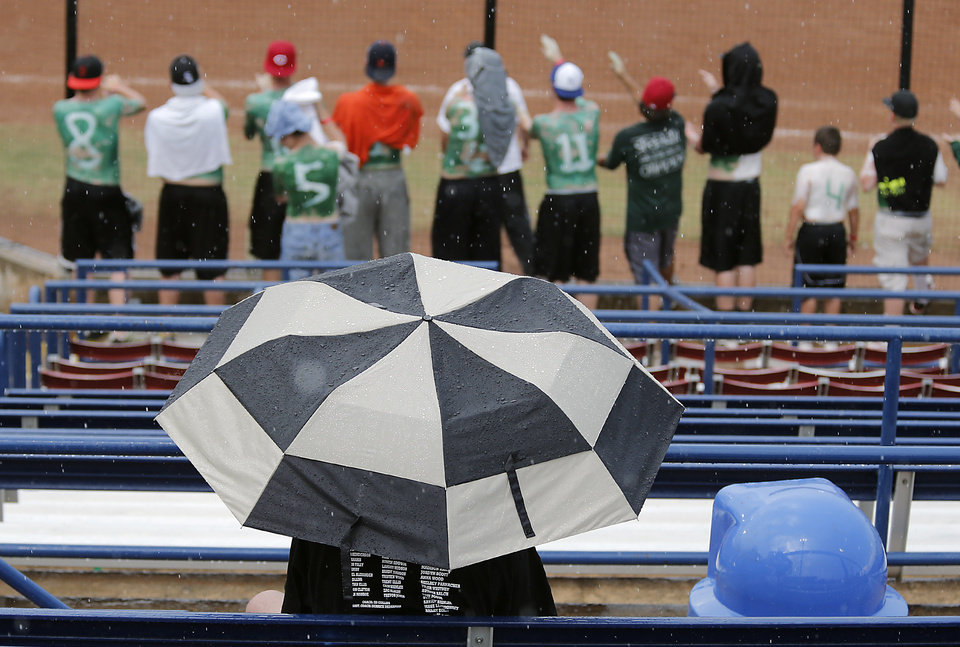 Photo - A softball fan braves the rain under an umbrella to watch the Class 4A Oklahoma State High School Slow Pitch Softball Championship at ASA Hall of Fame Stadium in Oklahoma City, Wednesday, May 1, 2013. Photo by Chris Landsberger, The Oklahoman