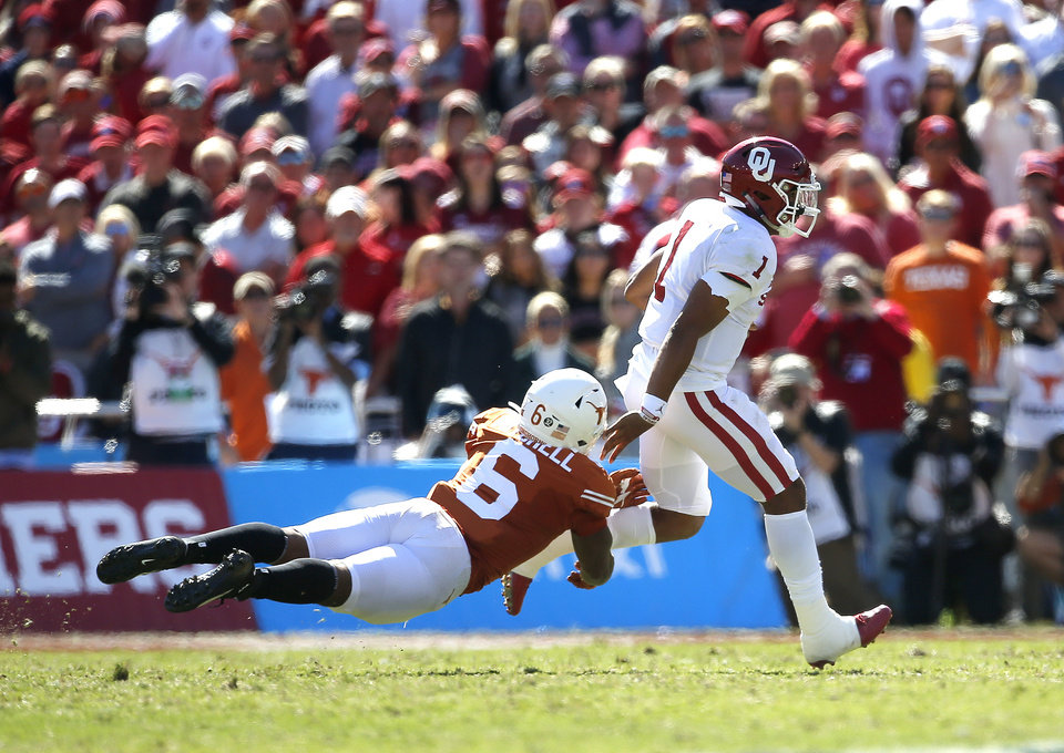Photo - Oklahoma's Jalen Hurts (1) rushes as Texas's Juwan Mitchell (6) tries to tackle him in the second quarter during the Red River Showdown college football game between the University of Oklahoma Sooners (OU) and the Texas Longhorns (UT) at Cotton Bowl Stadium in Dallas, Saturday, Oct. 12, 2019. OU won 34-27. [Sarah Phipps/The Oklahoman]