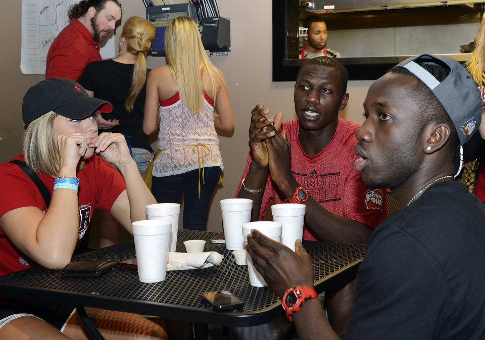 Photo - Louisville center Gorgui Dieng watches a broadcast of the women's team playing Connecticut in the NCAA Final Four college basketball tournament championship game in New Orleans, Tuesday, April 9, 2013, with friends at Cluckers Bar in Louisville, Ky. (AP Photo/Timothy D. Easley)