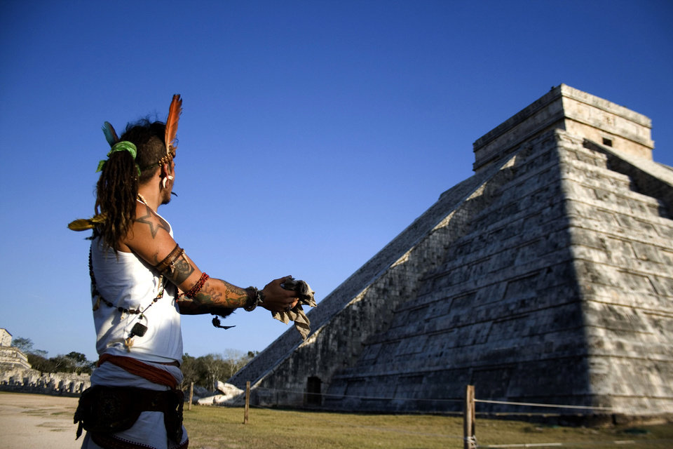 FILE - In this March 20, 2010 file photo, a man performs a ritual as he looks toward the descent of the Kukulkcan serpent, whose image is seen illuminated along the edge of the stairs of the Mayan Chichen Itza pyramid, during the Spring equinox in Chichen Itza, Mexico. A chorus of books and movies tried to link the Mayan calendar to rumors of impending disasters ranging from rogue black holes and sun-storms to the idea that the Earth\'s magnetic field could \'flip\' on that date. Archaeologists says there is no evidence the Maya ever made any such prophesy. (AP Photo/Israel Leal, File)
