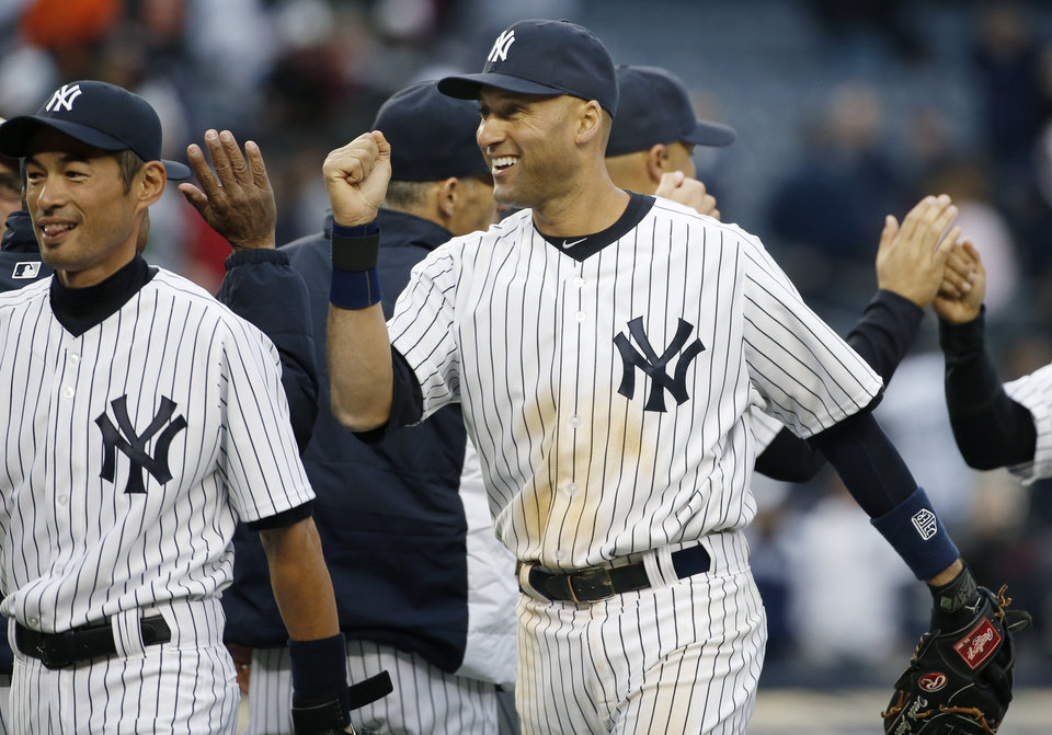 Photo - New York Yankees right fielder Ichiro Suzuki, left, and shortstop Derek Jeter celebrate the Yankees 4-2 victory over the Baltimore Orioles in the Yankees home  MLB American League baseball opener against the Baltimore Orioles, at Yankee Stadium in New York, Monday, April 7, 2014.  The Yankees defeated the Orioles 4-2. (AP Photo/Kathy Willens)