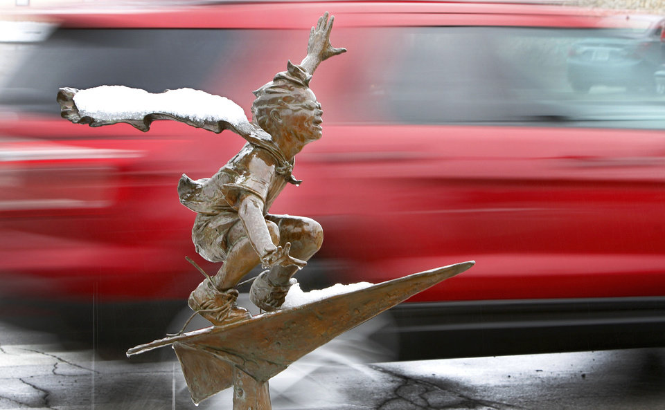 "Photo - Above: Snow decorates Edmond's ""Paper Airplane"" bronze statue Wednesday at Broadway and Main as a motorist drives past."