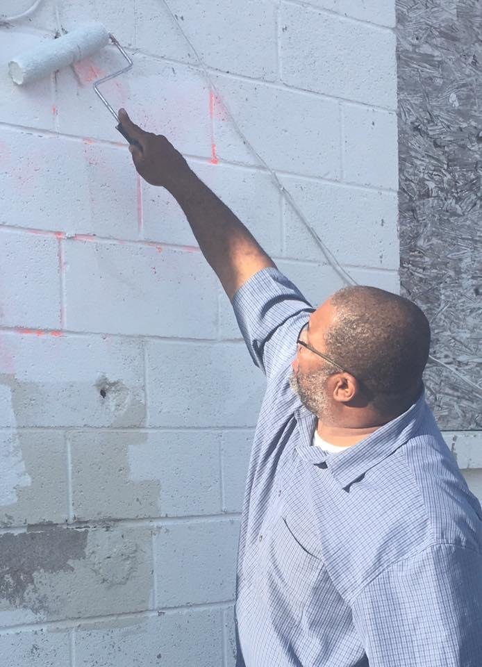 Photo -  Oklahoma City area Muslim leader Saad Mohammed paints over anti-Muslim statements that vandals spray-painted on the exterior of a Muslim-owned grocery store in northwest Oklahoma City. [Photo provided]