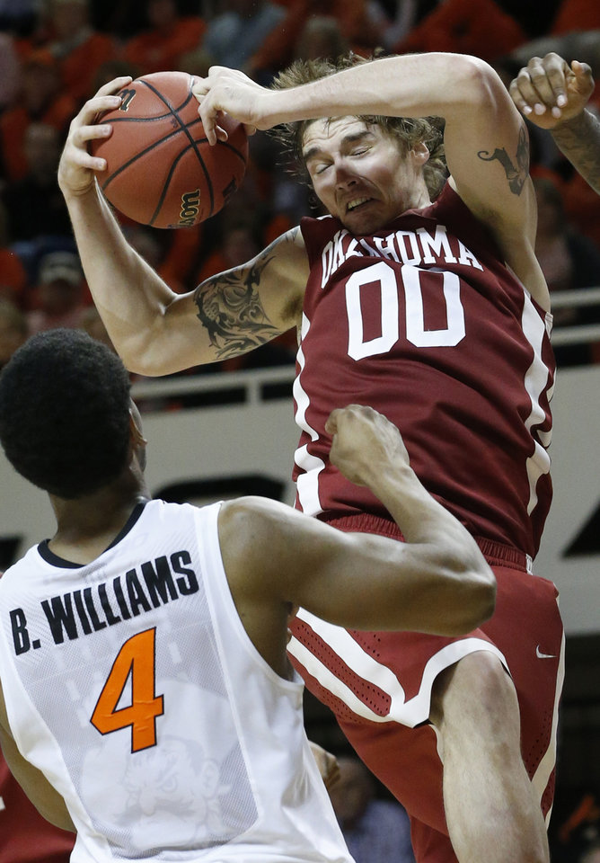 Photo - Oklahoma forward Ryan Spangler (00) grabs a rebound in front on Oklahoma State wing Brian Williams (4) in the second half of an NCAA college basketball game in Stillwater, Okla., Saturday, Feb. 15, 2014. Oklahoma won 77-74. (AP Photo/Sue Ogrocki)
