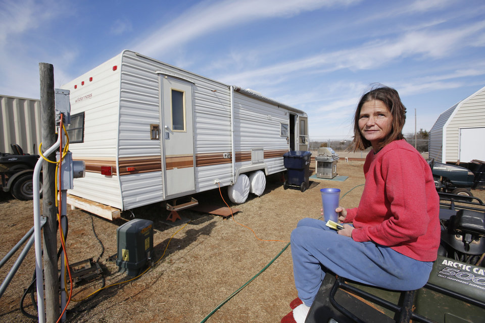 Photo - Tanya Lowry poses for a photo in front of her travel trailer on SE 119th near Lake Stanley Draper in Oklahoma City, Friday February  08, 2013. Lowry lost her long time lease to Oklahoma City to a company that has plans for a skeet shooting range. Photo By Steve Gooch, The Oklahoman