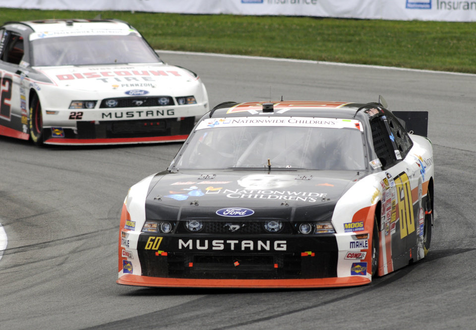 Photo - Chris Buescher (60) leads Alex Tagliani through a corner during the NASCAR Nationwide Series Nationwide Children's Hospital 200 auto race at Mid-Ohio Sports Car Course, Saturday, Aug. 16, 2014, in Lexington, Ohio. (AP Photo/Tom E. Puskar)