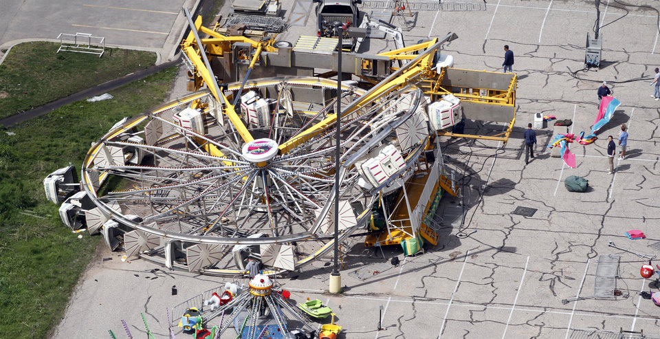Photo -   RE-TRANS FOR IMPROVED TONING - Workers check out the carnival that was damaged on Sunday, April 15, 2012, in Wichita, Kan. The carnival was game aged by one of several tornadoes that hit the state on Saturday, April 14, 2012. (AP Photo/Jeff Tuttle)