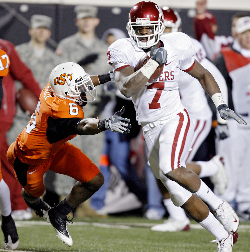 Photo - Oklahoma's DeMarco Murry (7) gets running room past Oklahoma State's Ricky Price (6) during the first half of the college football game between the University of Oklahoma Sooners (OU) and Oklahoma State University Cowboys (OSU) at Boone Pickens Stadium on Saturday, Nov. 29, 2008, in Stillwater, Okla. STAFF PHOTO BY CHRIS LANDSBERGER