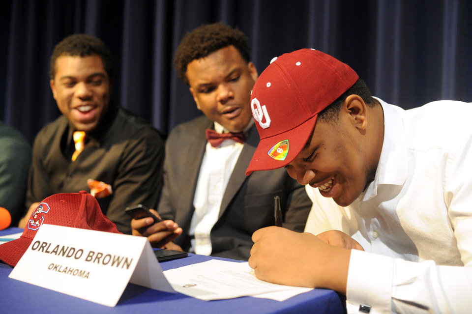 Photo - Oklahoma signee Orlando Brown, from Duluth, Ga., signs his National Letter of Intent on Wednesday at a signing ceremony at Peachtree Ridge High School. PHOTO BY BRENDAN SULLIVAN, Courtesy Gwinnett Daily Post