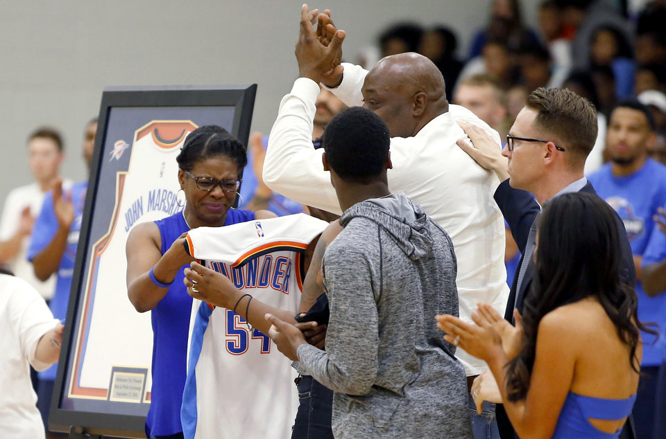 Photo - Lisa Roberts, mother of John Marshall Mid-High School student C.J. Davis who died in 2015, is presented with a Thunder jersey with her son's name on it before the Thunder's annual Blue and White Scrimmage at John Marshall Mid-High School in Oklahoma City, Tuesday, Sept. 27, 2016. Photo by Bryan Terry, The Oklahoman