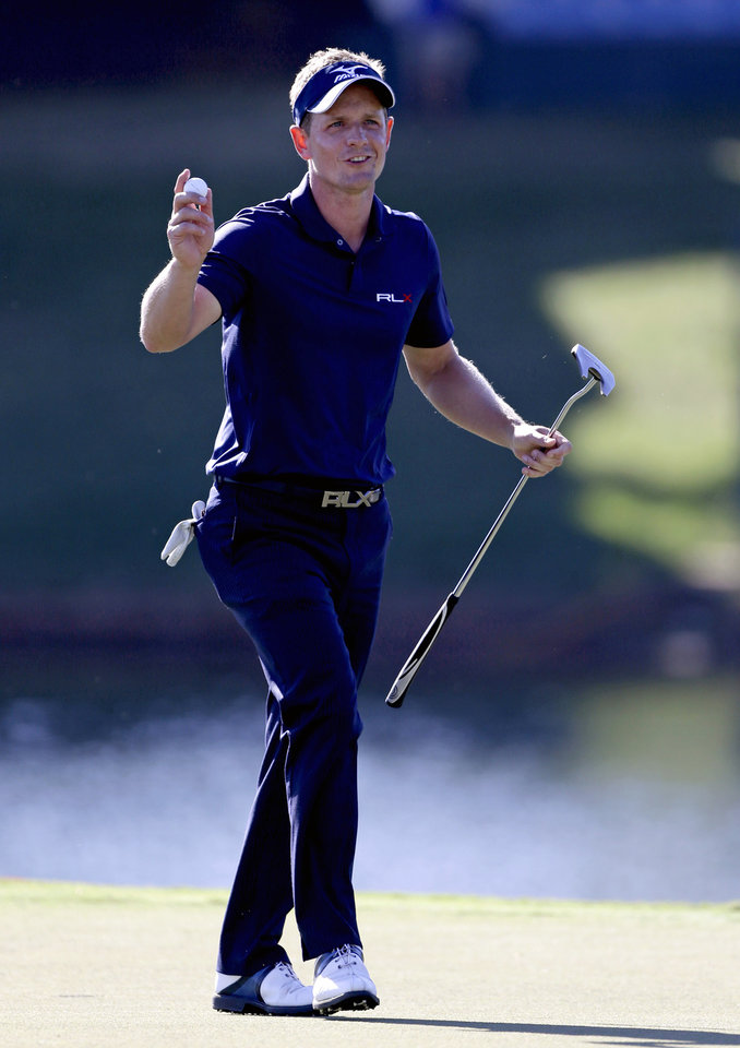 Photo -   Luke Donald, of England, acknowledges the applause from the crowd after sinking his putt on the 17th hole during the final round of the Tour Championship golf tournament Sunday, Sept. 23, 2012, in Atlanta. (AP Photo/David Goldman)