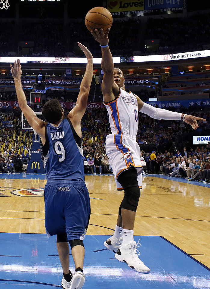 Photo - Oklahoma City's Russell Westbrook (0) shoots a lay up in front of Minnesota's Ricky Rubio (9) during the NBA game between the Oklahoma City Thunder and the Minnesota Timberwolves at the Chesapeake Energy Arena, Sunday, Dec. 1, 2013. Photo by Sarah Phipps, The Oklahoman