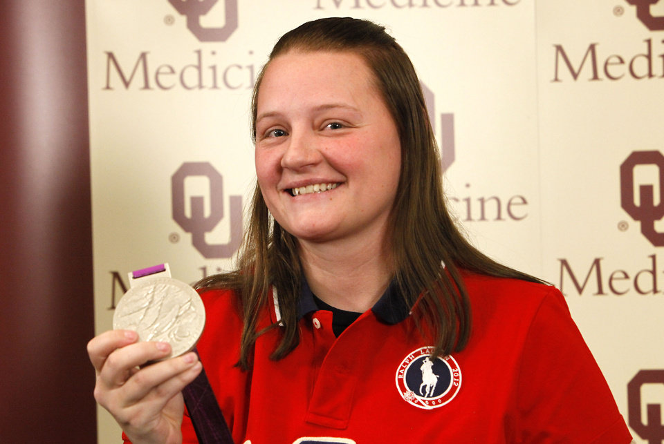 Photo - Monique Burkland with her paralympic silver medal  at a press conference at Children's Hospital, Tuesday, November 27, 2012. Burkland had her leg amputated after a forklift accident and Ertl helped her with her recovery.  Photo By David McDaniel/The Oklahoman