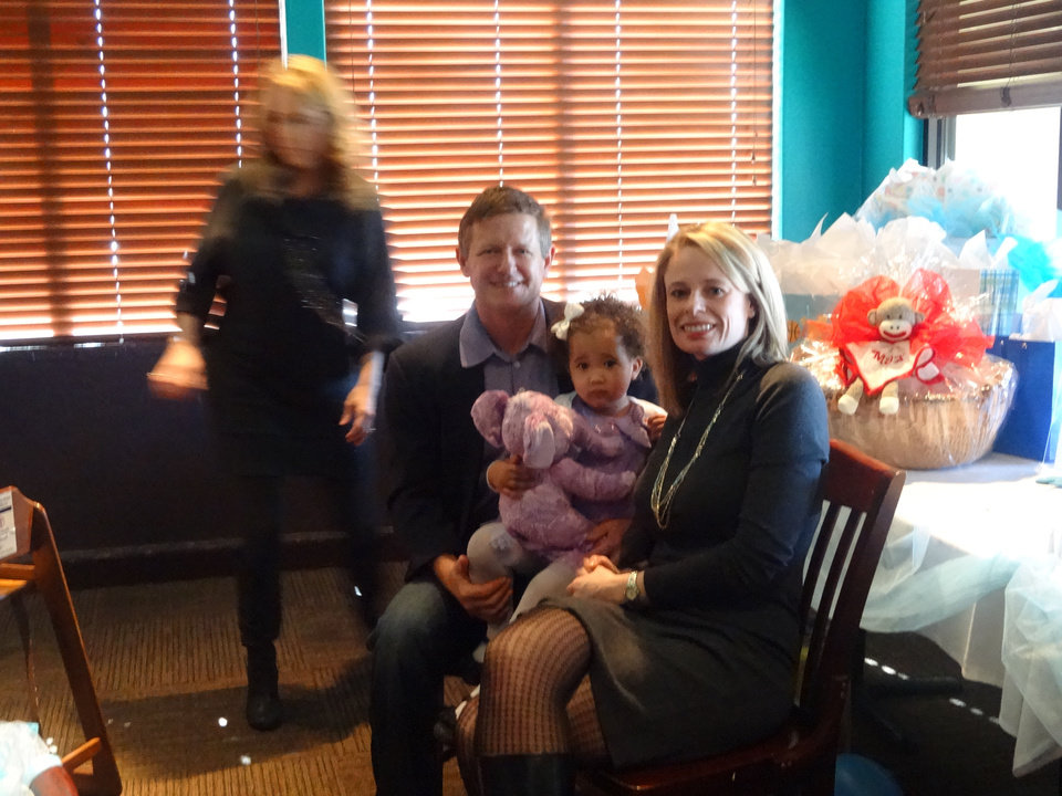 Bill and Alicia Towler hold their daughter Ashlyn, 2, at a recent surprise baby shower. The couple are due to adopt a boy next month. PHOTO PROVIDED