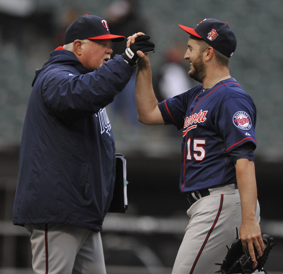 Photo - Minnesota Twins manager Ron Gardenhire, left, celebrates with closing pitcher Glen Perkins (15) after they defeated the Chicago White Sox 10-9 in a baseball game in Chicago, Thursday, April 3, 2014. (AP Photo/Paul Beaty)
