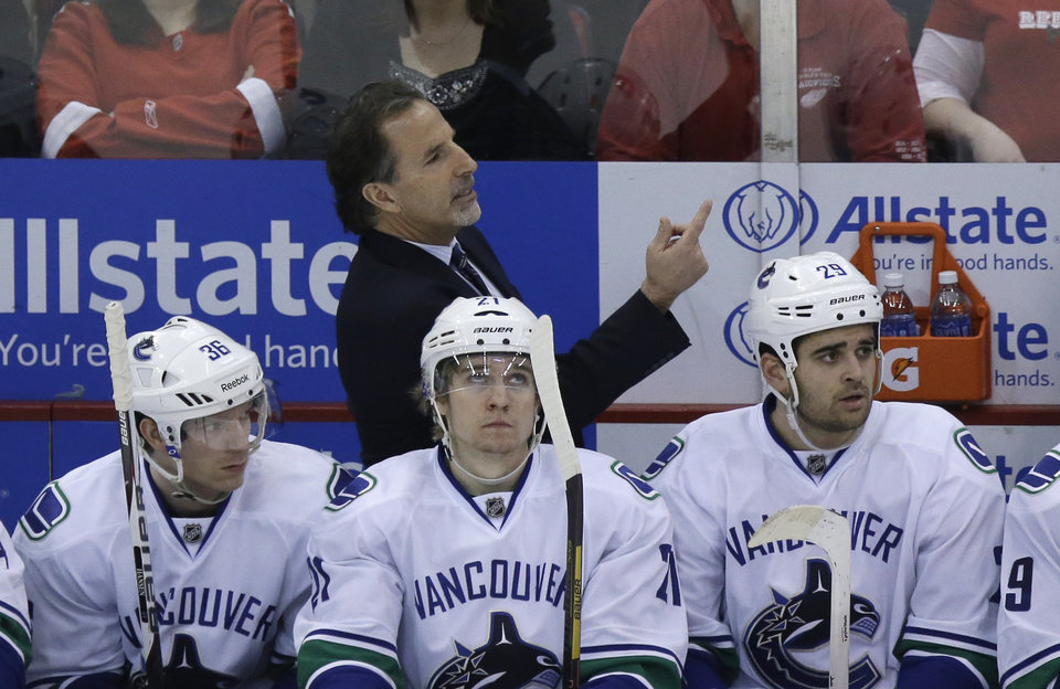 Photo - Vancouver Canucks head coach John Tortorella signals from the bench during the third period of an NHL hockey game against the Detroit Red Wings in Detroit, Monday, Feb. 3, 2014. (AP Photo/Carlos Osorio)