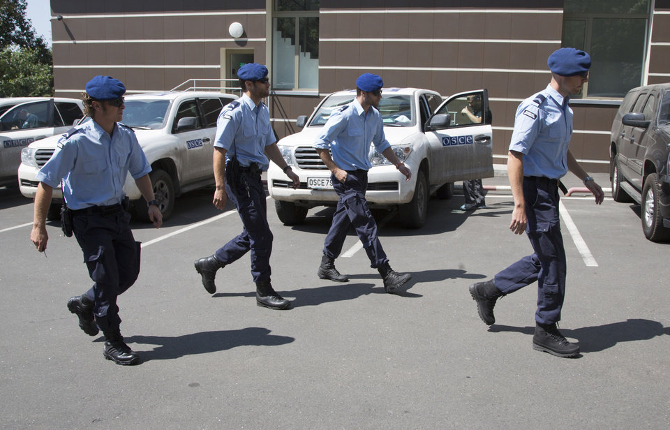 Photo - Dutch policemen walk to their cars in the city of Donetsk, eastern Ukraine Sunday, July 27, 2014. A team of international police officers that had been due to visit the site of the Malaysian plane disaster in eastern Ukraine cancelled the trip Sunday after receiving reports of fighting in the area. Alexander Hug, the deputy head of a monitoring team from the OSCE in Europe, said it would be too dangerous for the unarmed mission to travel to the site from its current location in the rebel-held city of Donetsk. (AP Photo/Dmitry Lovetsky)