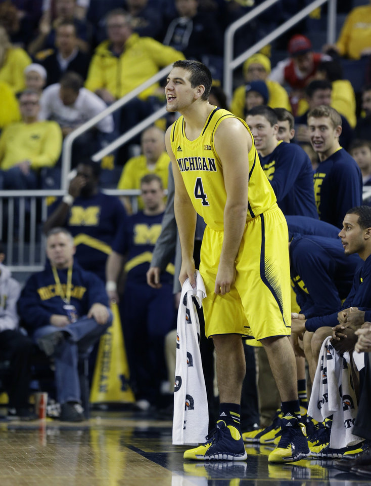 Photo - Michigan forward Mitch McGary yells from the sidelines during the second half of an NCAA college basketball game against Arizona in Ann Arbor, Mich., Saturday, Dec. 14, 2013. (AP Photo/Carlos Osorio)