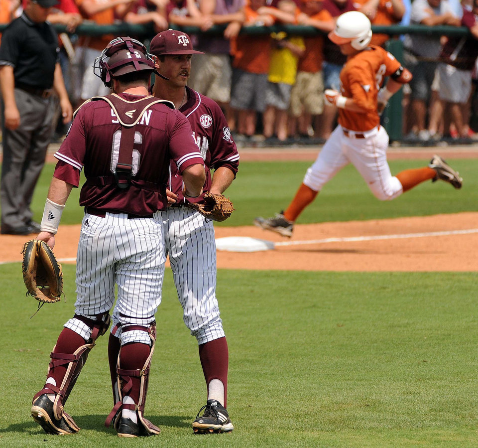 Photo - Texas A&M pitcher Daniel Mengden, center, talks with catcher Troy Stein, left, as Texas' Brooks Marlow, right, touches third base after hitting a solo home run during the first inning of an NCAA college baseball tournament regional game Friday, May 30, 2014, at Reckling Park in Houston. (AP Photo/Houston Chronicle, Eric Christian Smith) MANDATORY CREDIT
