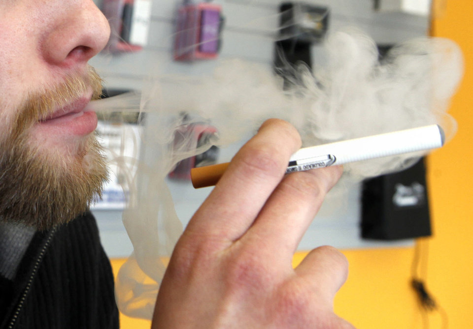 Photo -  A sales associate demonstrates the use of an electronic cigarette and the smoke-like vapor that comes from it in Aurora, Colo. Young people, including middle school and high school students, are increasingly trying electronic cigarettes, according to a recent CDC study. Provided photo   Ed Andrieski -  AP