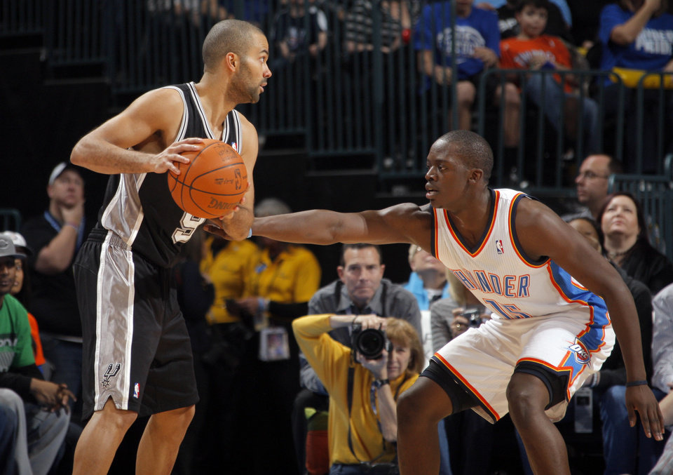 Photo - Oklahoma City Thunder's Reggie Jackson (15) defends San Antonio Spurs' Tony Parker (9) during the the NBA basketball game between the Oklahoma City Thunder and the San Antonio Spurs at the Chesapeake Energy Arena in Oklahoma City, Sunday, Jan. 8, 2012. Photo by Sarah Phipps, The Oklahoman
