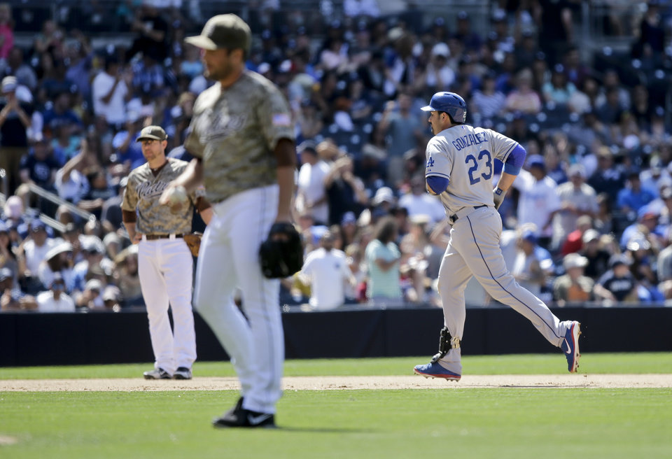 Photo - Los Angeles Dodgers' Adrian Gonzalez (23) rounds the bases with his ninth-inning home run as San Diego Padres closer Huston Street gather himself in a baseball game won by the Dodgers 3-1 in San Diego, Sunday, June 23, 2013. (AP Photo/Lenny Ignelzi)