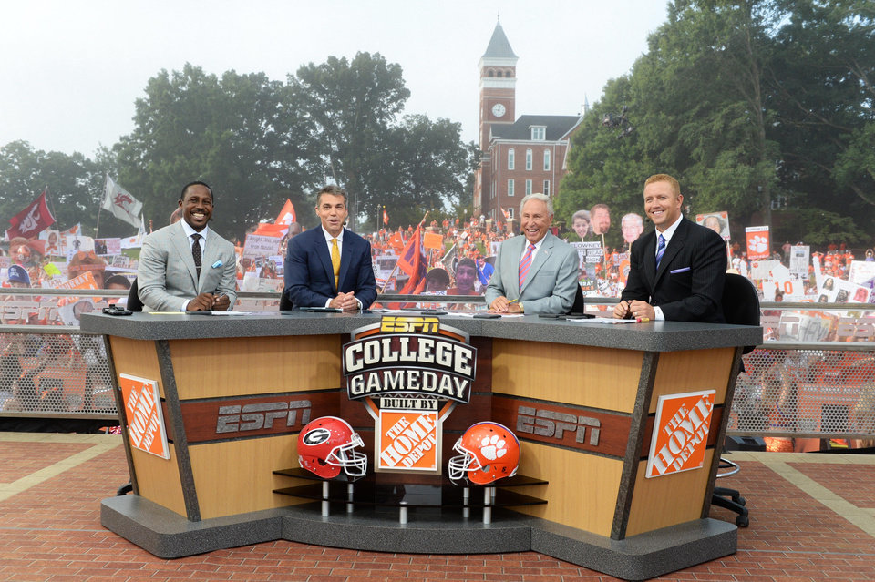 Photo - In this photo taken on Aug. 31, 2013, and provied by ESPN, from left, Desmond Howard, Chris Fowler, Lee Corso and Kirk Herbstreit smile on the set of College GameDay at Clemson Memorial Stadium in Clemson, S.C. ESPN is taking its College GameDay show to Fargo Saturday, Sept. 21, 2013, for North Dakota State's game against Delaware State. Some Bison fans are ecstatic while others are grumbling about ESPN setting up downtown near the Fargo Theatre instead of the Fargodome, where dozens of green and yellow coach buses and other homemade party wagons tailgate. (AP Photo/Courtesy ESPN Images, Allen Kee)