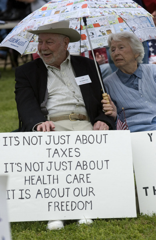 Photo - PROTEST / TEA PARTY RALLY / DE HAMPTON: De & Shirley Hampton, Grove, weather the cold and rainy weather Saturday to attend the Tea Party at the Grove Community Center in Grove.  Gary Crow/For the Oklahoman