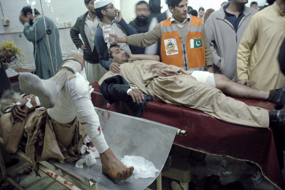 Injured victims of a suicide bombing are treated at a local hospital in Peshawar, Pakistan, Saturday, Dec. 22, 2012. A suicide bomber in Pakistan killed several people including a provincial government official at a political rally held Saturday by a party that has opposed the Taliban, officials said. (AP Photo/Mohammad Sajjad)