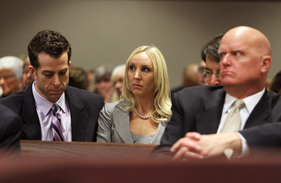 Photo - Nicole Oulson, center, listens to the taped interview of former Tampa Police captain Curtis Reeves, Jr., during his bond reduction hearing before Circuit Judge Pat Siracusa at the Robert D. Sumner Judicial Center in Dade City Friday, Feb. 7, 2014. Reeves is suspected of fatally shooting Chad Oulson, 43, and wounding Nicole, Oulson, during an argument Jan. 13 over texting at the Cobb Grove 16 theater in Wesley Chapel, Fla.  (AP Photo/Pool Tampa Bay Times, Brendan Fitterer, Pool)