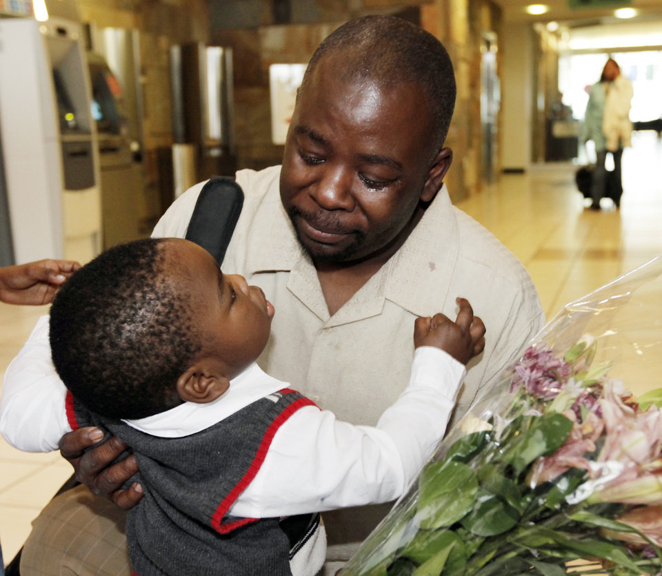Photo - Humphreys Munai greets his 19-month-old son, Austin Munai, after arriving at Will Rogers World Airport in Oklahoma City, Thursday, January 14, 2010. Humphreys Munai was returning from Haiti where he was working for World Neighbors when the recent earthquake devastated the country. Photo by Nate Billings, The Oklahoman