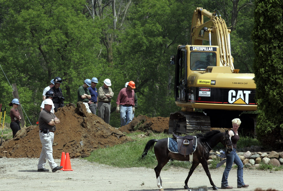 Photo -   FILE - In this May 25, 2006, file photo, excavation crews dig up the site of a horse barn that was demolished as part of the FBI's search for the remains of Jimmy Hoffa in Milford Township, Mich. (AP Photo/Carlos Osorio, File)