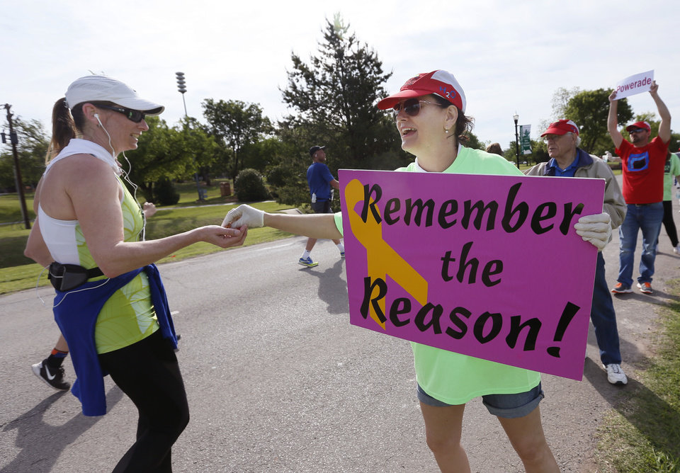 Photo - Kathy Frankenfield hands pretzels to a runner at the Pelco and Kirkpatrick Bank water stop along Grand Blvd. during the Oklahoma City Memorial Marathon in Nichols Hills, Sunday, April 24, 2016. Frankenfield said that she volunteers in honor of bombing victim Mike Weaver. Photo by Nate Billings, The Oklahoman