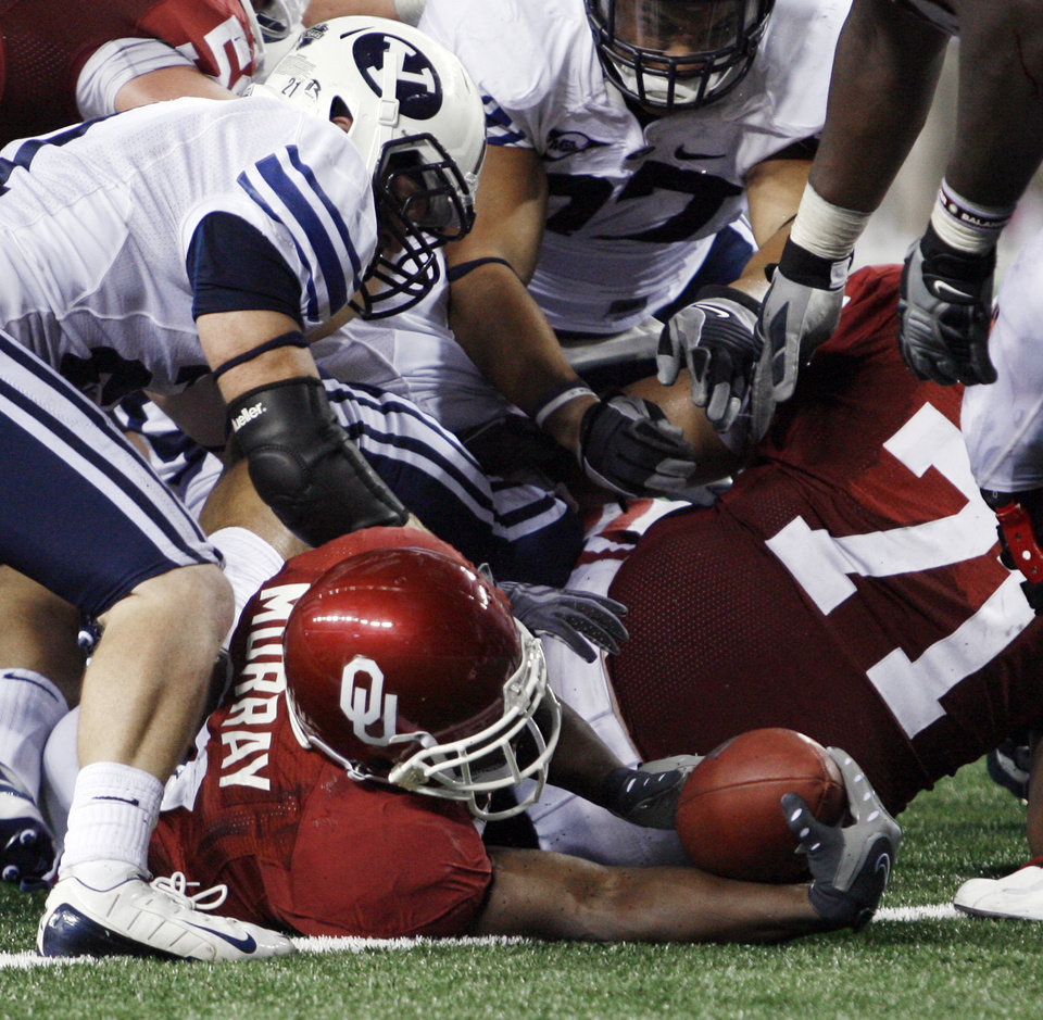 DeMarco Murray tries to extend the ball over the goal line on a run during second half action of the college football game between the Brigham Young University Cougars (BYU) and the University of Oklahoma Sooners (OU) at Cowboys Stadium in Arlington, Texas, Saturday, September 5, 2009. By Steve Sisney, The Oklahoman