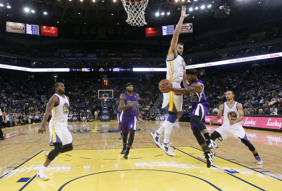 Photo - Sacramento Kings' Isaiah Thomas (22) passes to DeMarcus Cousins (15) as Golden State Warriors' Andrew Bogut, center, defends during the first half of an NBA preseason basketball game Monday, Oct. 7, 2013, in Oakland, Calif. (AP Photo/Marcio Jose Sanchez)