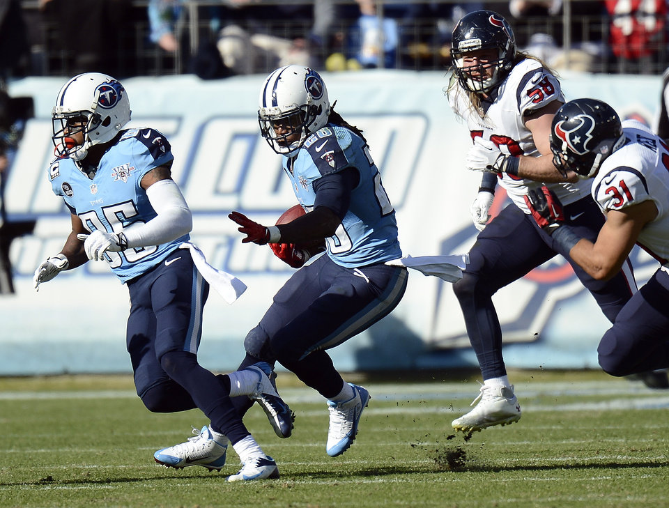 Photo - Tennessee Titans running back Chris Johnson (28) follows the blocking of Nate Washington (85) as he carries the ball against Houston Texans defenders Brooks Reed (58) and Shiloh Keo (31) in the second quarter of an NFL football game Sunday, Dec. 29, 2013, in Nashville, Tenn. Johnson passed 1,000 yards rushing for the season on the play. (AP Photo/Mark Zaleski)