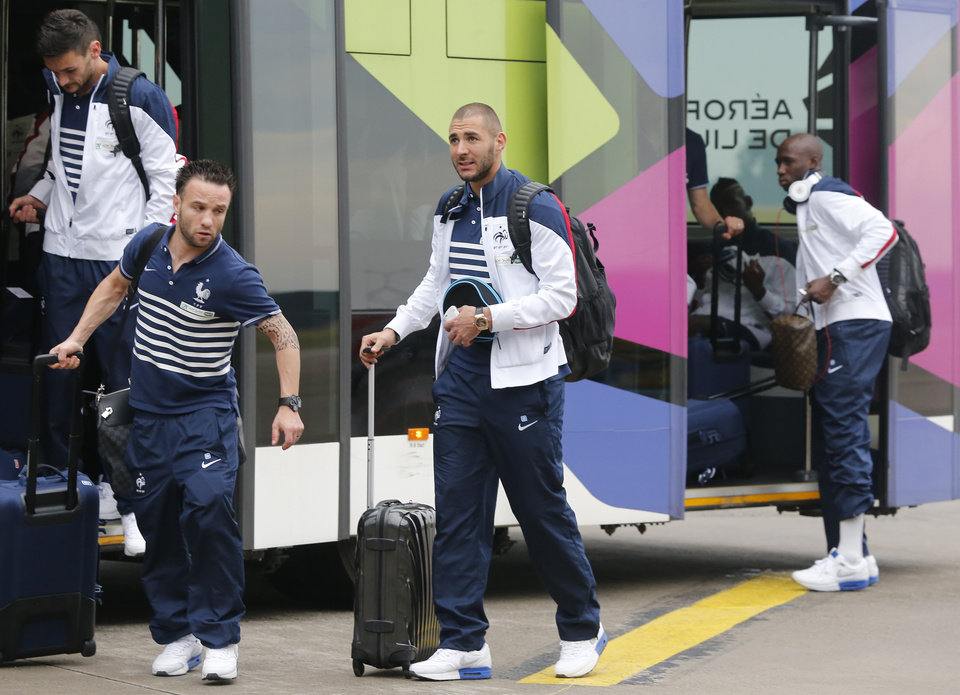 Photo - Members of France's soccer team, left from right, Hugo Lloris, Mathieu Valbuena, Karim Benzema and Rio Mavuda arrive at Lille -Lesquin  Airport as they prepare to travel to Brazil for the World Cup soccer tournament, in Lesquin northern France, Monday, June 9, 2014. France is part of Group E  that includes  Ecuador, Switzerland and Honduras. will play  Honduras in Porto Alegre in its opening match on June 15. (AP Photo/Jacques Brinon)