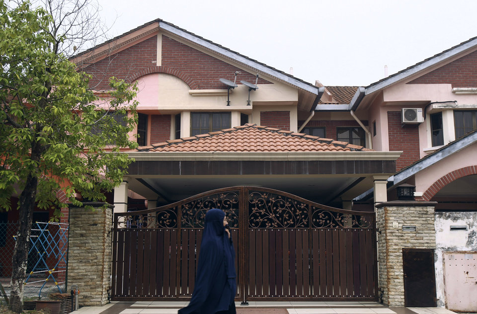Photo - A Muslim woman walks past the missing Malaysia Airlines co-pilot Fariq Abdul Hamid's house in Shah Alam, outside Kuala Lumpur, Malaysia, Friday, March 14, 2014. The pilots of the missing Malaysia Airlines passenger jet were a contented middle-aged family man passionate enough about flying to build his own simulator and the 27-year-old contemplating marriage who had just graduated to the cockpit of the Boeing 777. Details about the men have emerged from interviews with neighbors, Malaysia Airlines staff, a religious leader and from social networks and news reports in Malaysia and Australia. (AP Photo/Lai Seng Sin)
