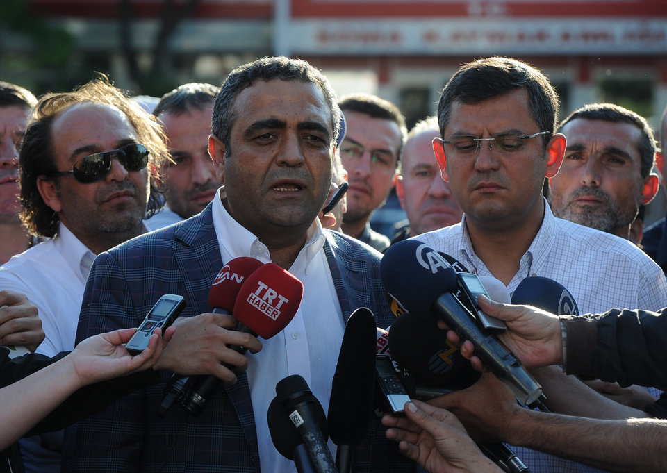 Photo - Opposition lawmakers Sezgin Tanrikulu, left, and Ozgur Ozel, right, speak to the media outside a local courthouse in the coal miners' town of Soma, Turkey, Sunday, May 18, 2014. Eighteen people, including mining company executives, have been detained as Turkish officials investigate the mining disaster that killed 301 people, a domestic news agency reported Sunday. The banner reads:
