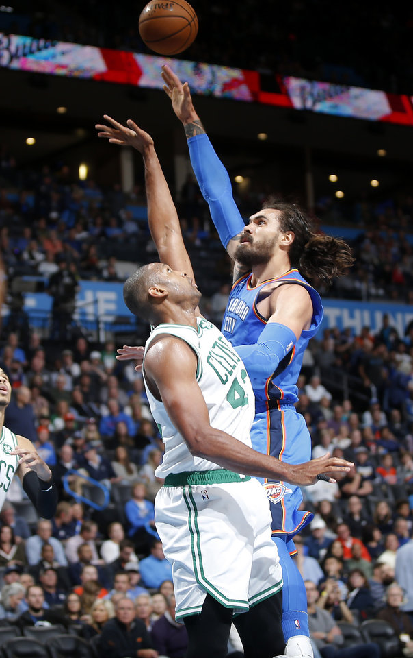 Photo - Oklahoma City's Steven Adams (12) shoots over Boston's Al Horford (42) during an NBA basketball game between the Oklahoma City Thunder and the Boston Celtics at Chesapeake Energy Arena in Oklahoma City, Thursday, Oct. 25, 2018. Photo by Bryan Terry, The Oklahoman