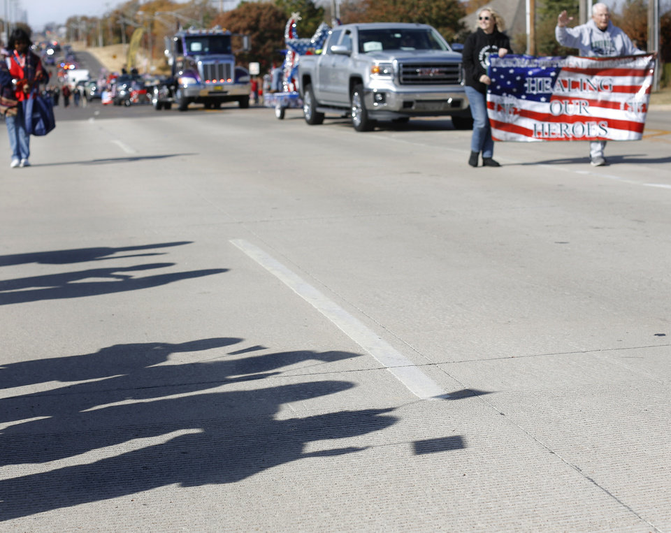 Photo - Shadows cast on SE 15 Street by children waving American flags as they watch  the Midwest City Veteran's Day Parade on Friday, Nov. 10, 2017. Photo by Jim Beckel, The Oklahoman
