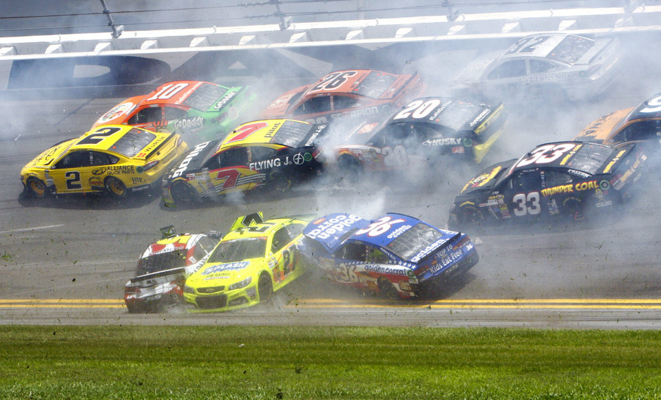 Photo - Kasey Kahne, front left, Paul Menard (27) and Reed Sorenson (36) are among the cars that crashed coming out of the backstretch going in to turn 3 during the NASCAR Sprint cup Series auto race at Daytona International Speedway in Daytona Beach, Fla., Sunday, July 6, 2014. (AP Photo/Ron Sanders)