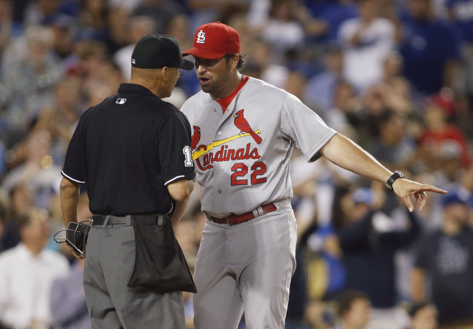 Photo - St. Louis Cardinals manager Mike Matheny, right, talks with home plate umpire Vic Carapazza after Cardinals' Jon Jay was called out at home plate during the seventh inning of a baseball game against the Los Angeles Dodgers, Thursday, June 26, 2014, in Los Angeles. The play was reviewed and the call stood. (AP Photo/Danny Moloshok)