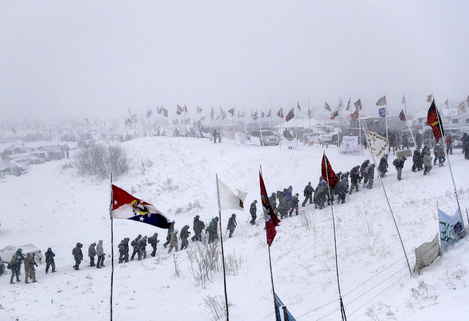 Photo - People walk out of the Oceti Sakowin camp as a march of military veterans and Native American tribal elders proceeds to a closed bridge across from the Dakota Access oil pipeline site in Cannon Ball, N.D., Monday, Dec. 5, 2016. (AP Photo/David Goldman)