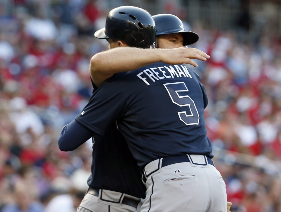 Photo - Atlanta Braves' Evan Gattis hugs Freddie Freeman after Freeman's solo home run during the first inning of a baseball game against the Washington Nationals at Nationals Park on Friday, June 20, 2014, in Washington. (AP Photo/Alex Brandon)