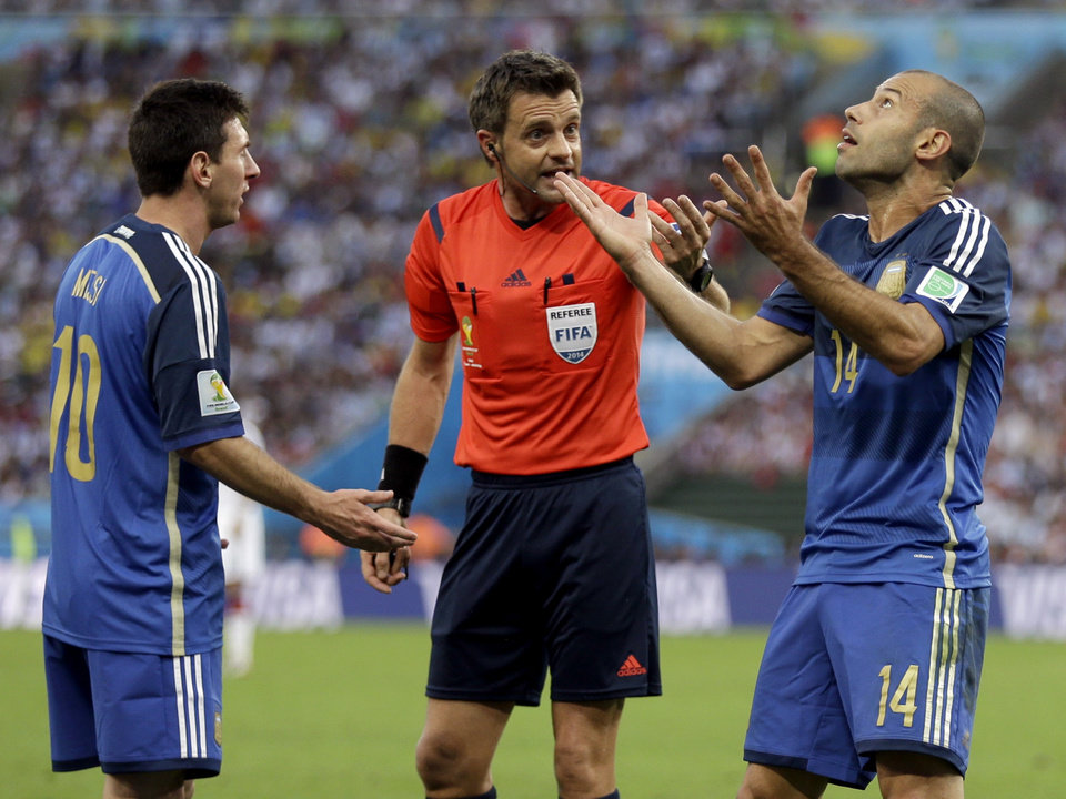 Photo - Argentina's Javier Mascherano (14) and Lionel Messi argue with referee Nicola Rizzoli from Italy after Gonzalo Higuain collided with Germany's goalkeeper Manuel Neuer during the World Cup final soccer match between Germany and Argentina at the Maracana Stadium in Rio de Janeiro, Brazil, Sunday, July 13, 2014. (AP Photo/Natacha Pisarenko)