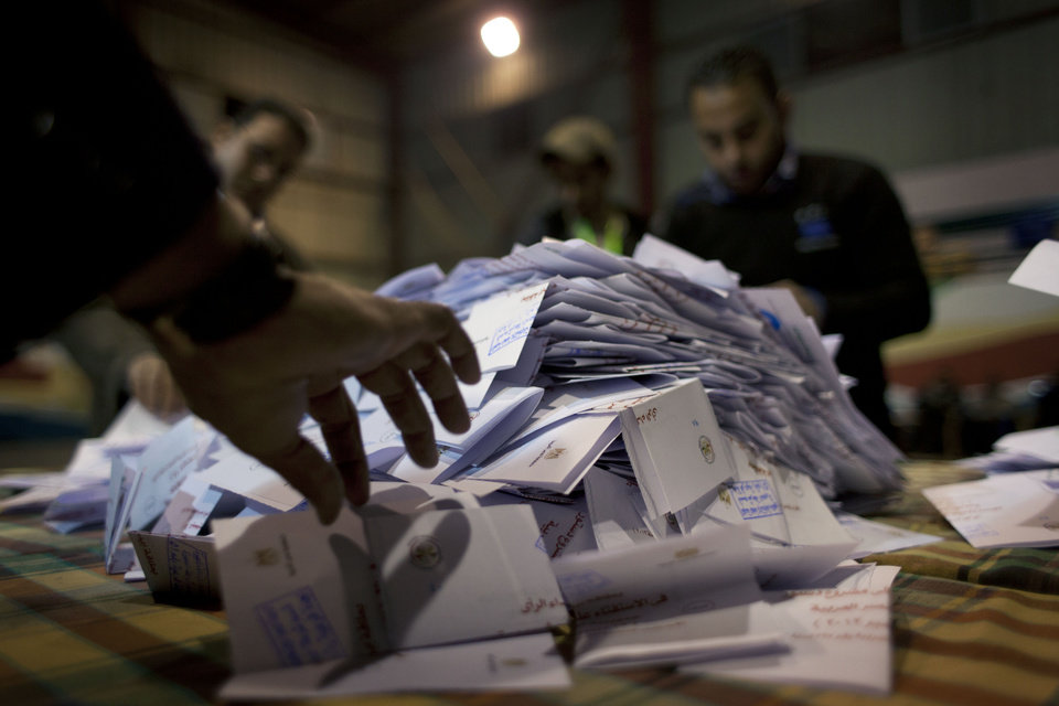 Photo - Egyptian election workers count ballots at the end of the second round of a referendum on a disputed constitution drafted by Islamist supporters of president Mohammed Morsi at a polling station in Giza, Egypt, Saturday, Dec. 22, 2012. Egypt's Islamist-backed constitution headed toward likely approval in a final round of voting on Saturday, but the deep divisions it has opened up threaten to fuel continued turmoil. (AP Photo/Nasser Nasser)